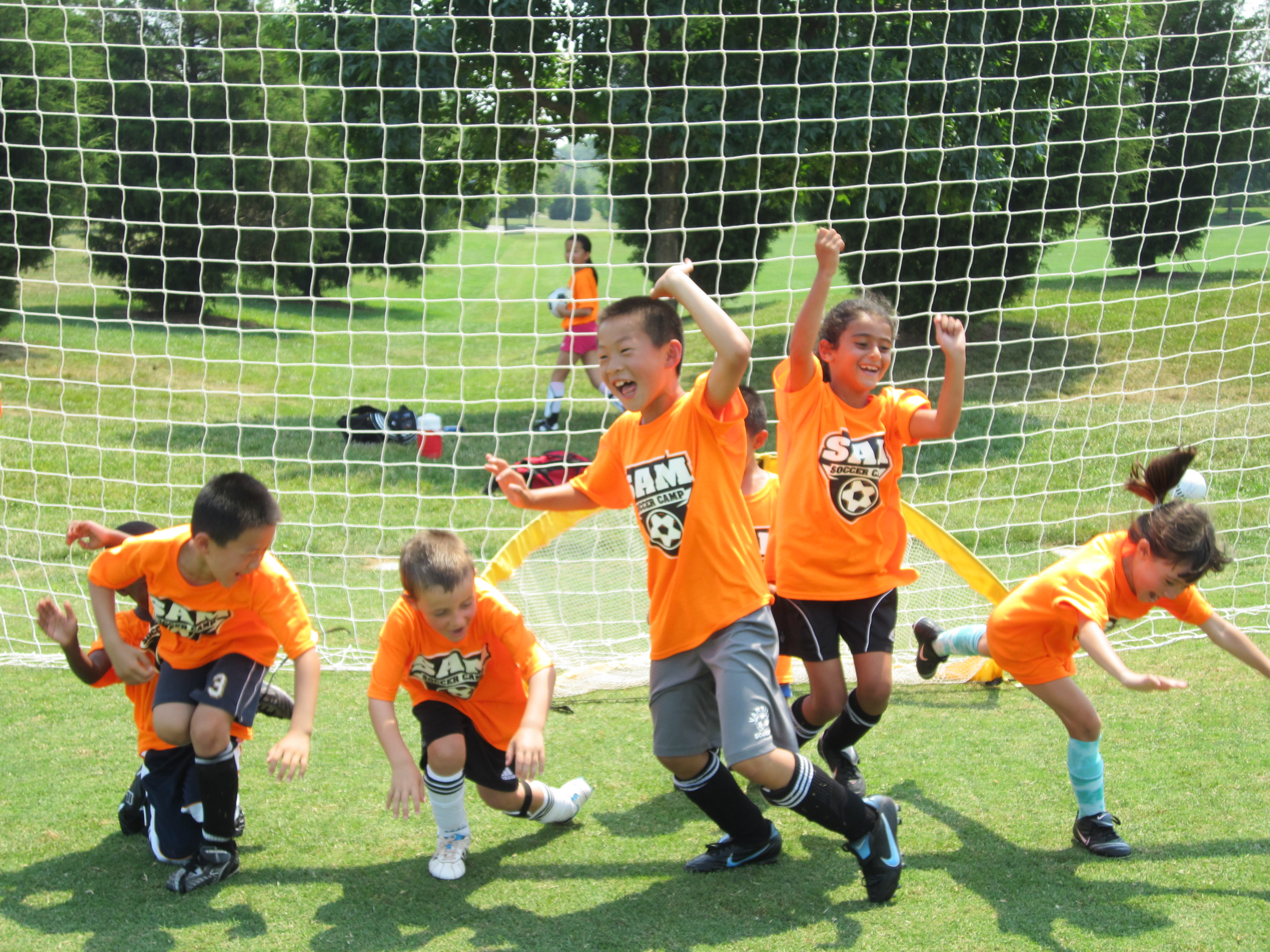 "alt=""Children jumping for joy at SAM Soccer Camp"""