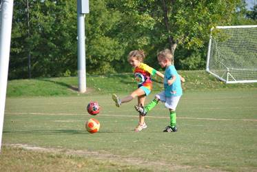 "alt=""2 Children kicking a ball"""